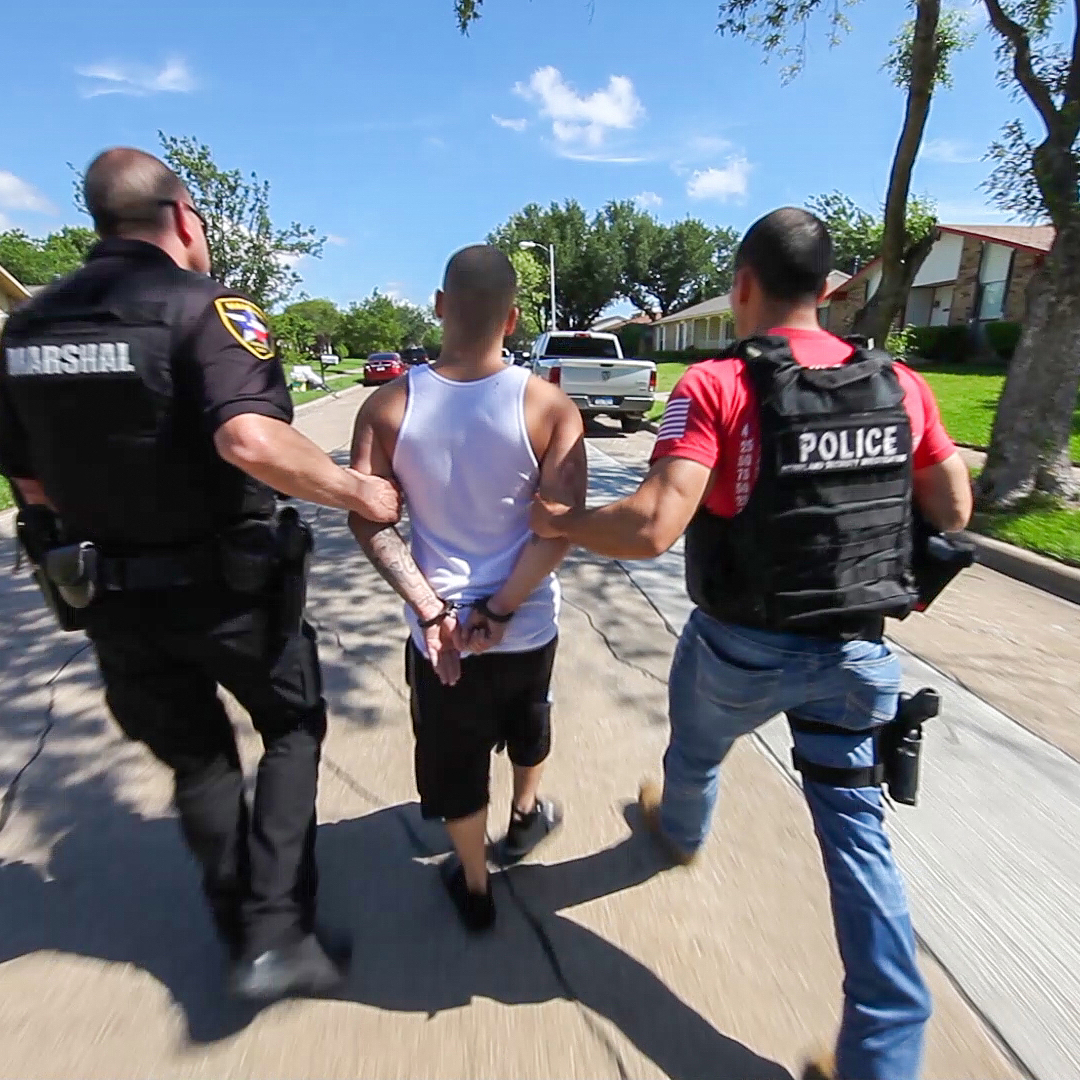 U.S. Immigration and Customs Enforcement (ICE) agents take a man into custody.