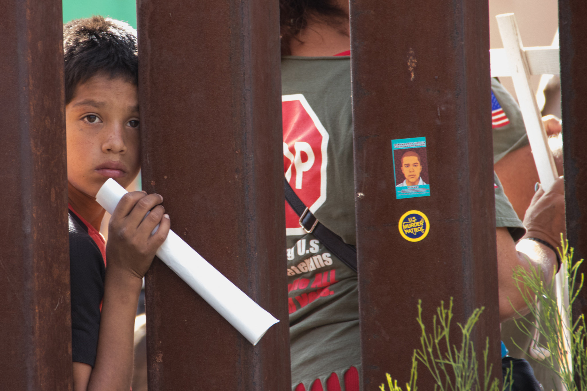 A boy peers through fencing at the U.S.-Mexico border.