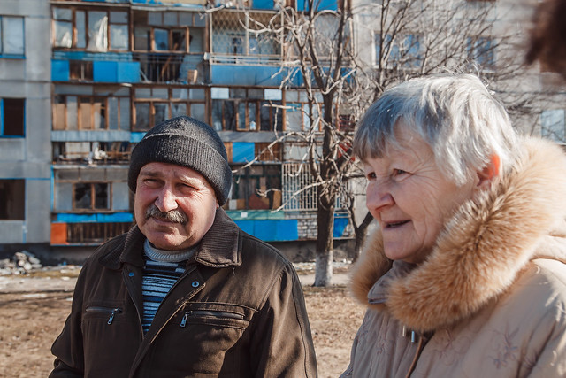 An older man and woman stand in front of an apartment building