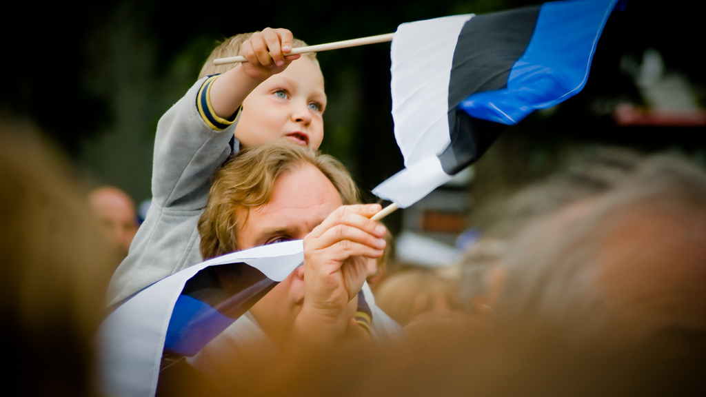 A father and son wave flags at the Estonian Song Festival in Tallinn.
