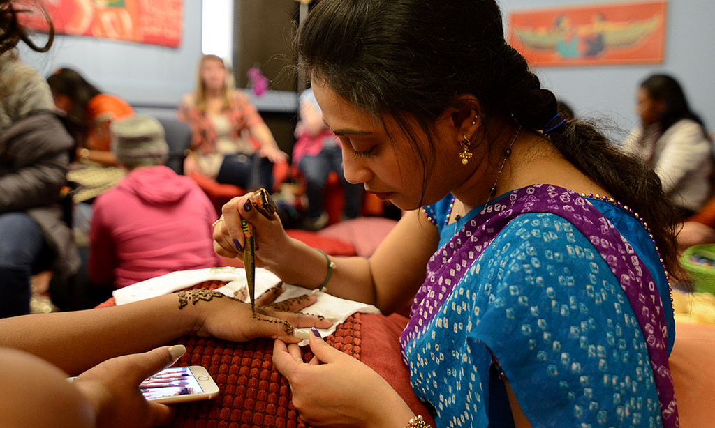 Indian college student applying henna.