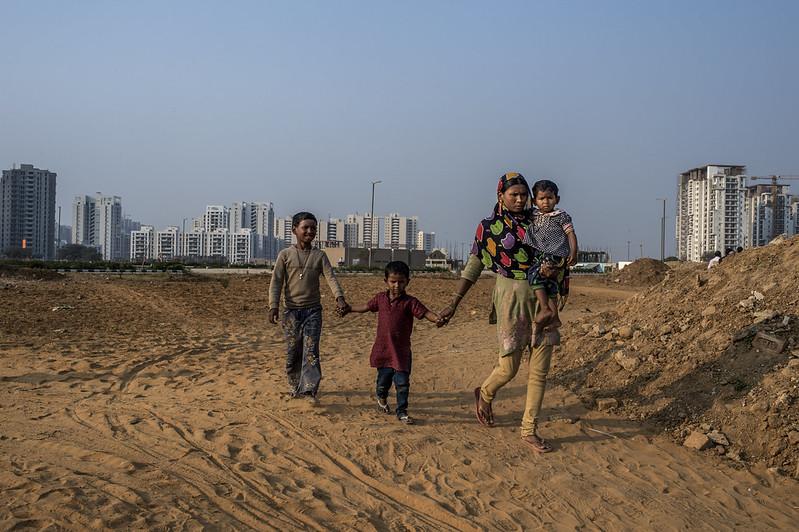 An Indian internal migrant walks with her children in Delhi