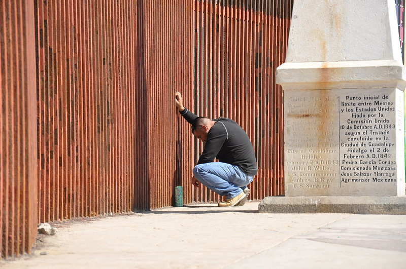 A man says goodbye to his partner through the border fence
