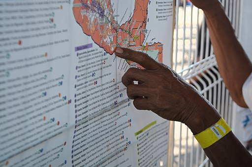 Migrant pointing at map of Mexico
