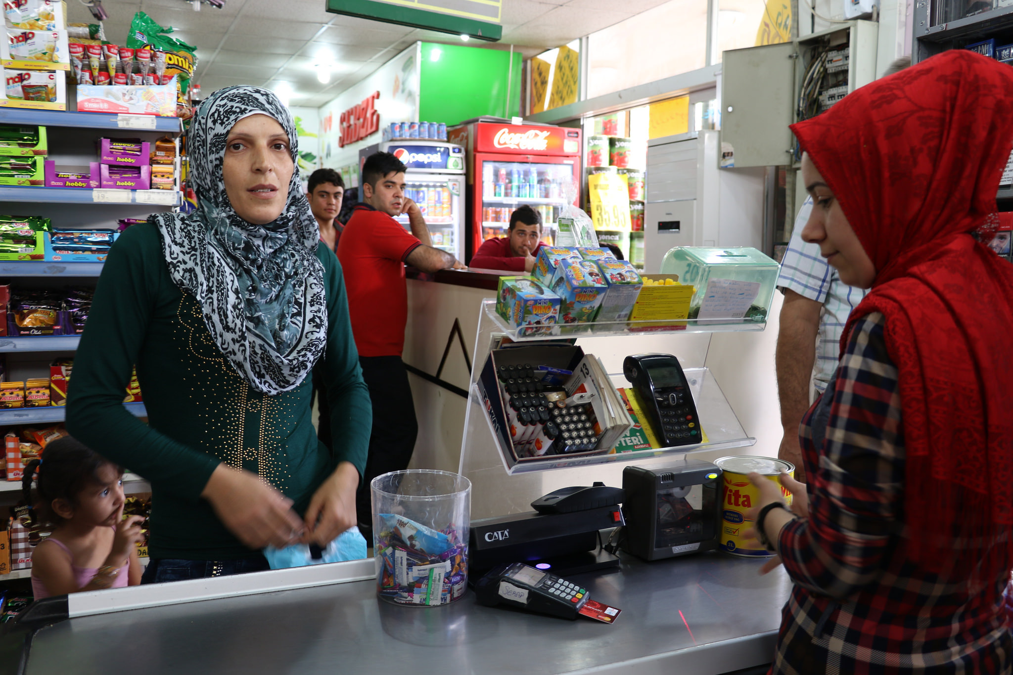 A Syrian refugee woman uses a special e-card to purchase food at a grocery store in Turkey.