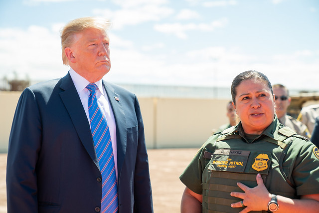 President Trump and a Customs and Border Patrol officer stand together