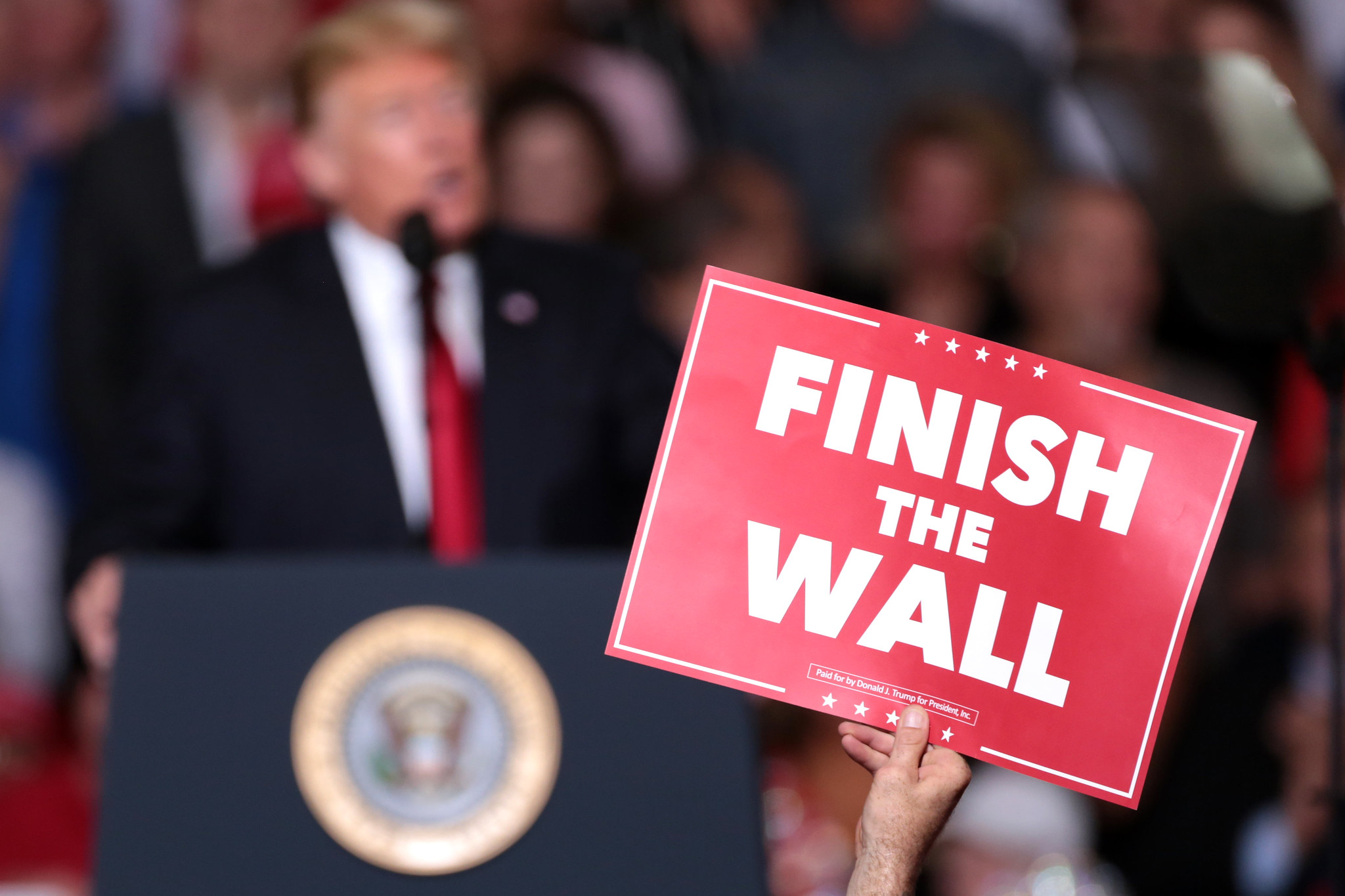 "A supporter holds a sign reading ""Finish the Wall"" during a rally for President Donald Trump in Mesa, Arizona."