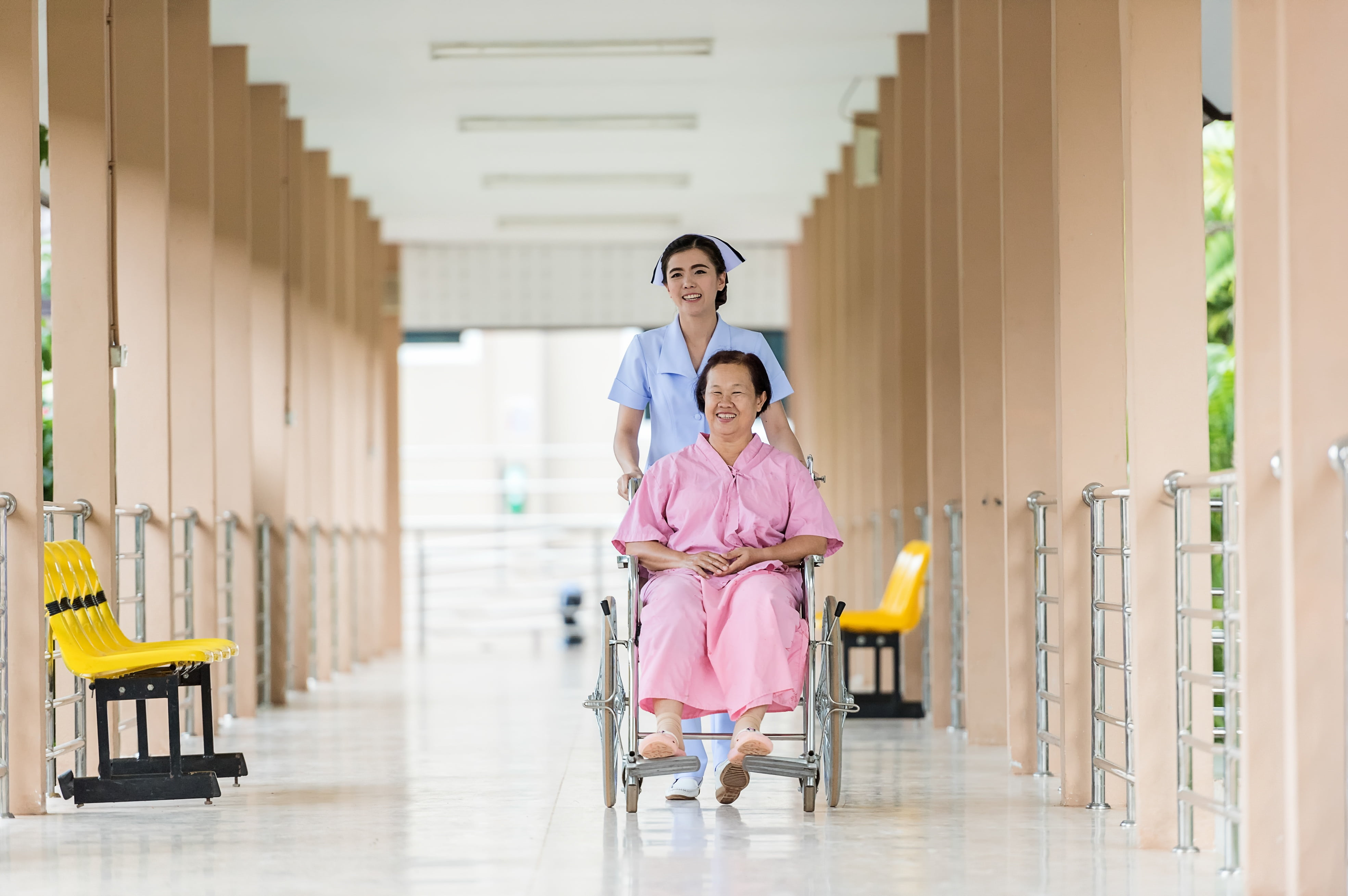 A nurse assists a woman in a wheelchair