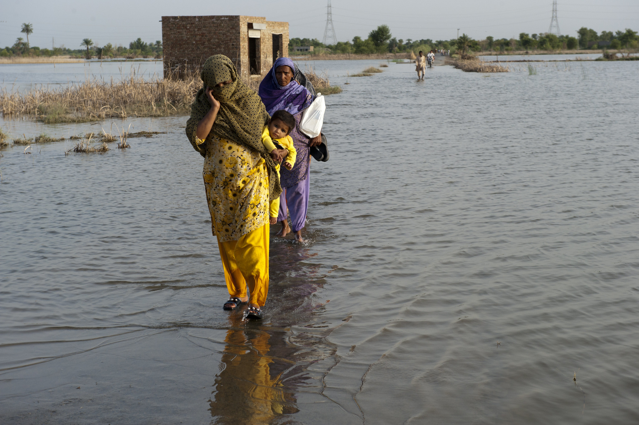 A family in Pakistan walks through flooded streets
