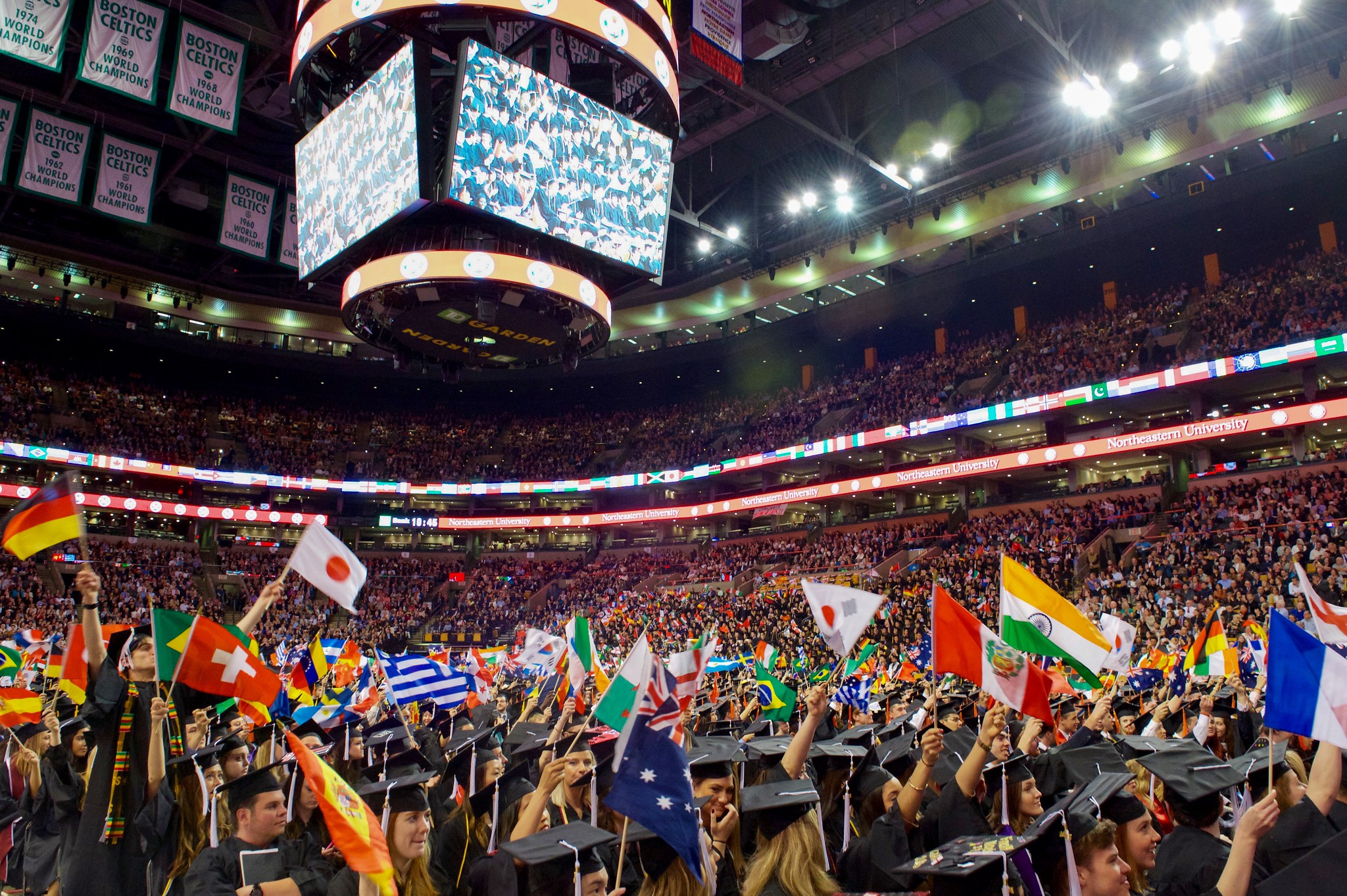 International students wave flags of their origin countries at a commencement address at Northeastern University