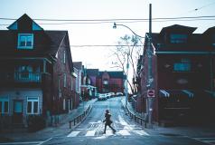 Woman walks across a street in a Toronto neighborhood