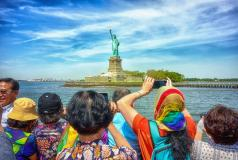 People take photos of the Statue of Liberty.