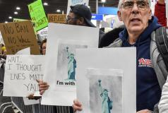 A man holds a sign protesting the travel ban at an airport