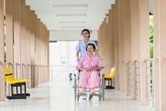 A nurse assists a woman in a wheelchair