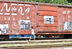 A woman walks alongside a train in Mexico.