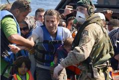 Sailors and marines on the HMS Bulwark help migrants ashore in Italy.