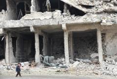 A child walks by a destroyed building in Syria.