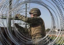 U.S. Marine secures barbed-wire fencing at the California-Mexico border.