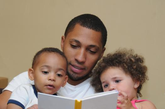 An immigrant father reading with his children.