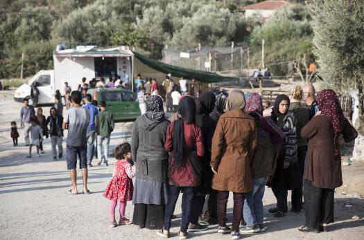 Asylum seekers standing outside at a camp in Lesbos, Greece