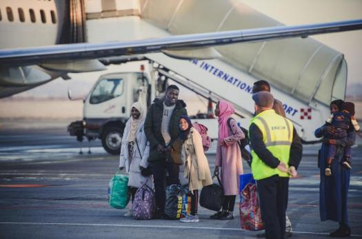 A family of refugees arriving at an airport during resettlement