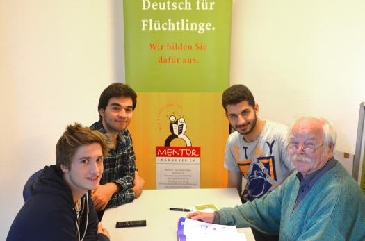 Syrian refugees meet with volunteers at a German for Refugees program.