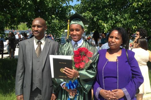 A refugee student with his family at graduation.