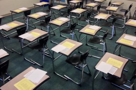A classroom with exam papers on students' desks