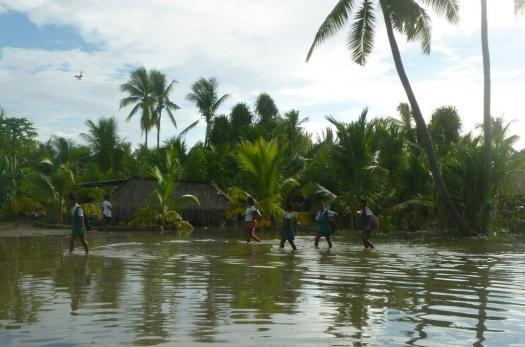 People walk through a flooded area in Kiribati