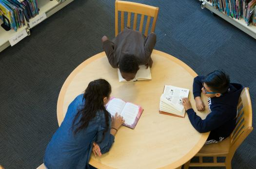Middle school students studying in a library