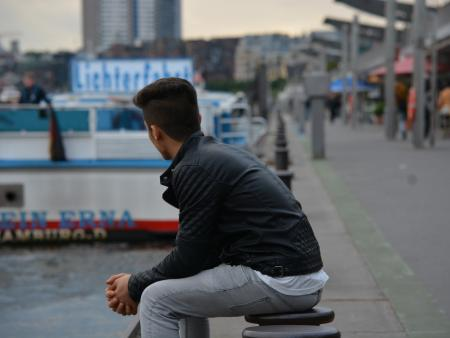 A refugee looks out over Hamburg harbor