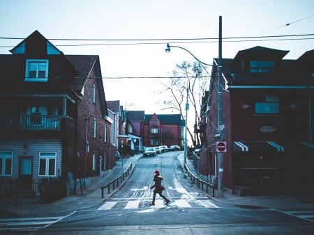Woman walks across a street in a Toronto neighborhood