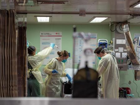Three health professionals wearing masks in a hospital