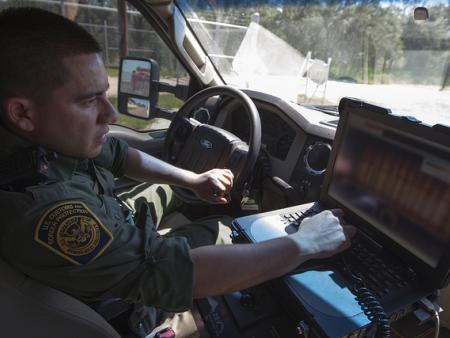 South Texas Border Patrol agent inspects a truck at a CBP checkpoint.