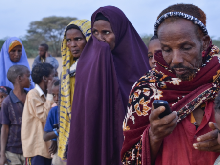 A refugee texts while waiting to register at Ifo refugee camp in Dadaab, Kenya.