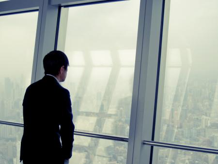 A Chinese businessman looks out over a hazy Shanghai.