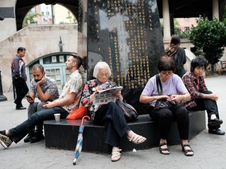Group of people sit in a park in New York's Chinatown