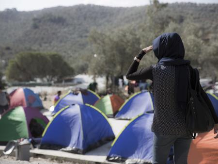 A woman looks out over tents being used by migrants and asylum seekers on the Greek island of Lesvos