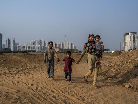 An Indian internal migrant walks with her children in Delhi